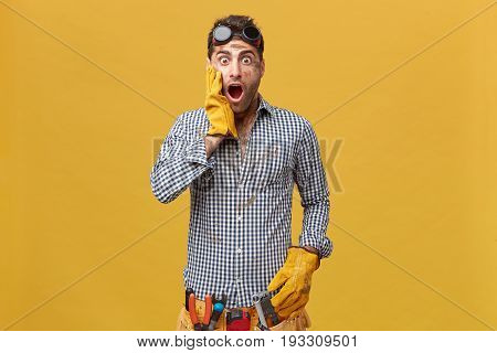Young Handsome Mechanic Wearing Protective Wear With Belt Of Tools Holding His Hand In Gloves On Che