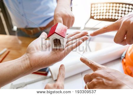 Teamwork Of Architectural Engineer Consulting On The Creation Of A Model Home, Hands Pointing To Min