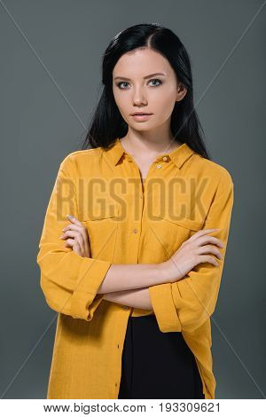 Attractive Brunette Woman With Crossed Arms Posing In Yellow Blouse, Isolated On Grey