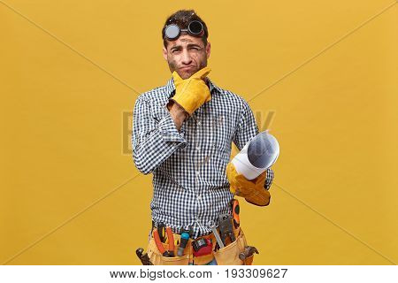 Portrait Of Male Fettler Wearing Protective Wear Holdinng Blueprint Having Thoughtful Expression Whi