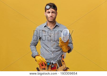 Serious Male Builder With Belt Of Instruments Wearing Checkered Shirt, Protective Eyeglasses And Glo