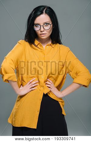 Beautiful Fashionable Woman Posing In Yellow Blouse And Stylish Glasses, Isolated On Grey