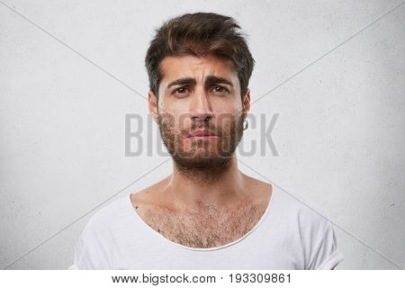 Stressed Bearded Male Having Sad Expression Wearing Earring And White T-shirt Curving His Lip Knowin