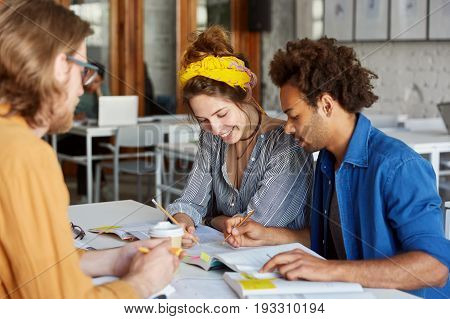 Group Of Three Interracial Students Meeting Together In Classroom Working With Books Writing Somethi