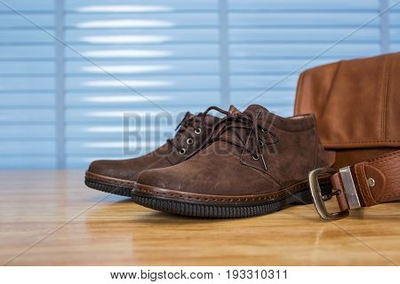 Men's Leather Fashion Clothing, Shoes, Bag And Belt On Plywood Table Desk In Business Office Room.