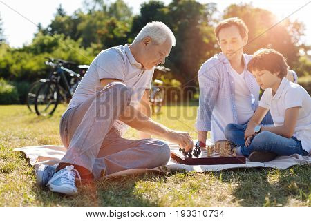 Developing thinking. Gifted wise aged man enjoying intellectual game while the boy thinking about his next move and being backed by his dad