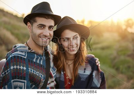 Couple Of Beautiful Girlfriend And Boyfriend In Black Hats Sitting On Grass At Meadow Smiling And Em