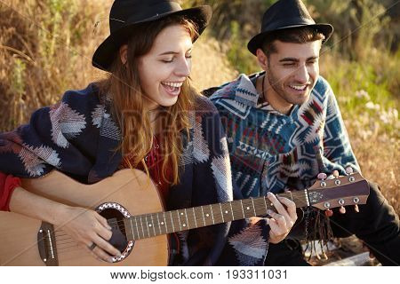 Attractive Female In Black Summer Hat Playing Guitar With Great Pleasure Singing Songs To Her Boyfri