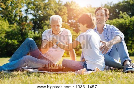 Enlightening kid. Dedicated wise aged gentleman brining chess to the picnic and trying involving his grandchild in this intellectual game