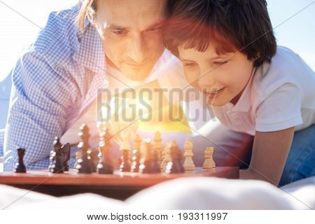 Adult game. Admirable intelligent talented parent teaching his child about the intellectual game while he trying building his strategy in chess