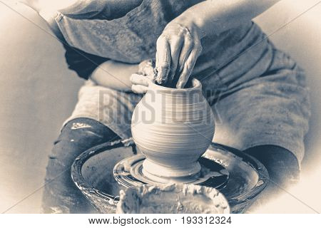 Photo in old vintage style. Girl sculpts in clay pot closeup. Modeling clay close-up.