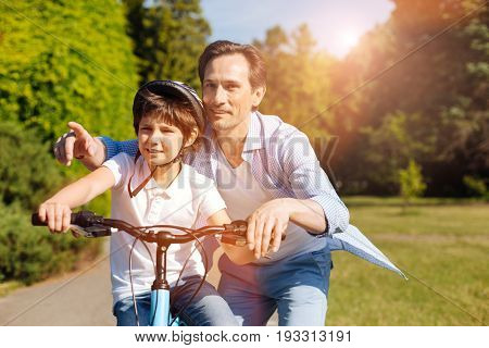 Maybe there. Bright energetic positive family choosing the direction they moving further while taking his child outdoors and teaching him how riding a bike