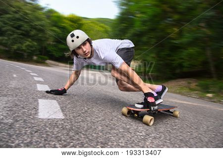 Young man in helmet is going to slide, slide with sparks on a longboard on the asphalt