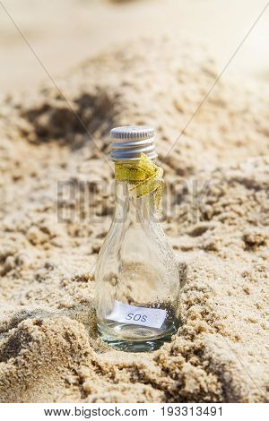 SOS message in glass bottle on the beach.