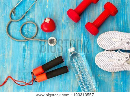 Fitness equipment gym workout and fresh water with heart and medical stethoscope on the blue background. Healthy Concept.