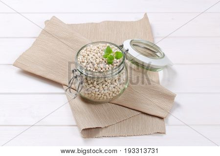jar of raw white beans on beige place mat