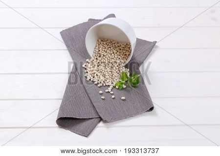 bowl of raw white beans spilt out on grey place mat