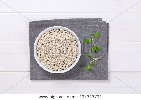 bowl of raw white beans on grey place mat
