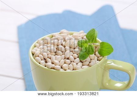 cup of raw white beans on blue place mat - close up