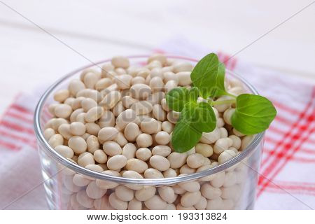 glass of raw white beans on checkered dishtowel - close up