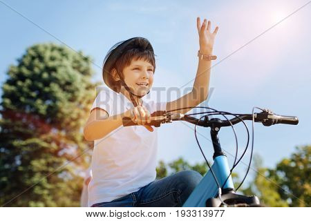 Hey there. Bright incredible sincere child spotting his friend and greeting him while meeting for a bike ride together