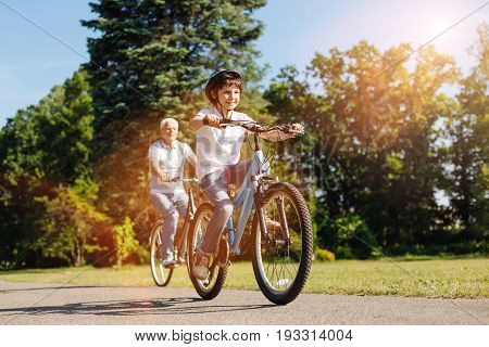 Increasing speed. Inventive easy going nice kid and his grandparent having fun while spending his day with his grandpa and riding bikes with him