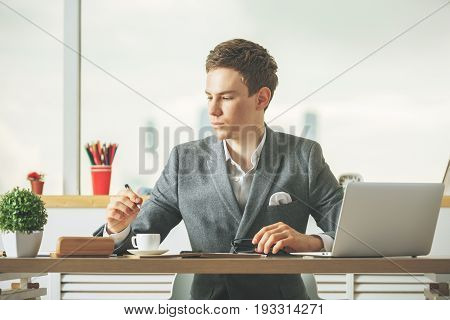 Attractive caucasian boy drinking coffee and using laptop in modern office with blurry city view and items on desktop