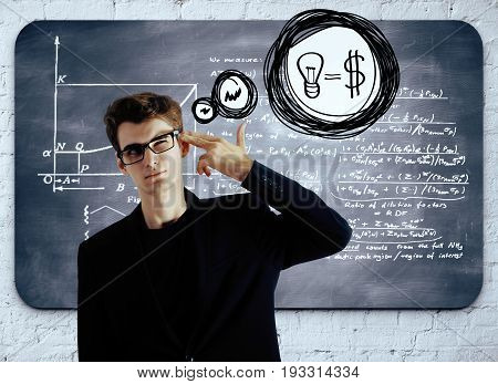 Thoughful businessman with head put to temple as a gun standing in front of chalkboard with mathematical formulas. Financial ideas concept