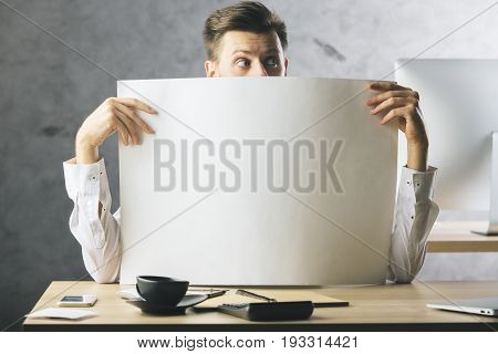 Surprised businessman covering face with huge empty paper sheet. Mock up