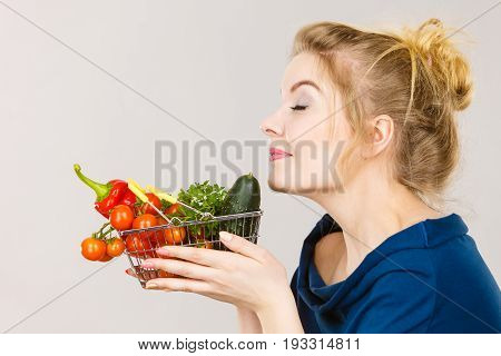 Buying good food vegetarian products. Attractive woman holding shopping basket with green red vegetables inside smelling with eyes closed recommending healthy high fibre diet on grey