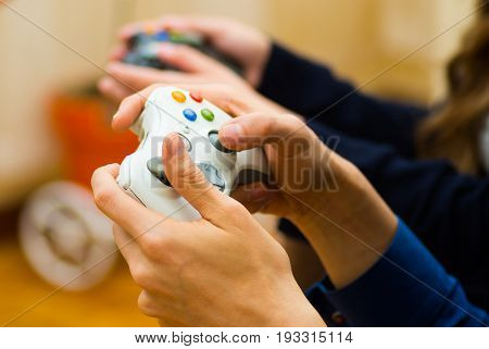 Close up hand holding a gamepad to play video games on the couch, concept about home entertainment, video games.