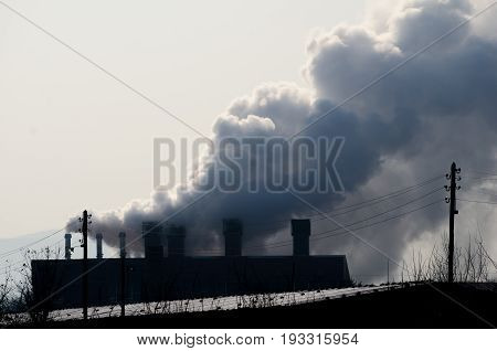 Pollution. Multiple coal fossil fuel power plant smokestacks emit carbon dioxide pollution. Dark image. Hard contrast. With film grain