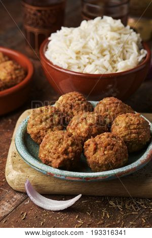 some falafel in a green earthenware plate and a brown earthenware bowl with long grain rice on a rustic wooden table, with some ornamented glasses with tea in the background