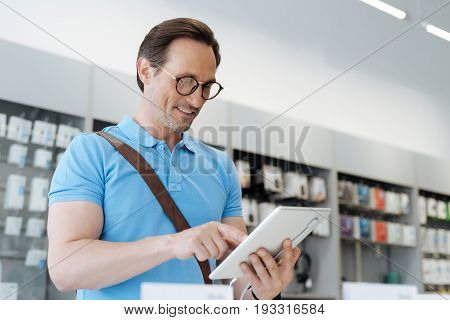 This one is real dream. Male shopper looking for a new gadget and trying out all the technological capabilities of a tablet computer while shopping at an electronics store.