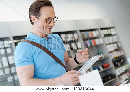 I am in disbelief. Brown haired man wearing glasses smiling while holding and testing a template tablet t an electronics section of a department store.