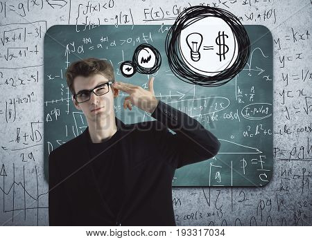 Thoughful businessman with head put to temple as a gun standing in front of chalkboard with mathematical formulas. Sales increase ideas concept