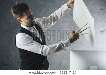 Crazy beast man about to tear paper sheet with pencils held as claws