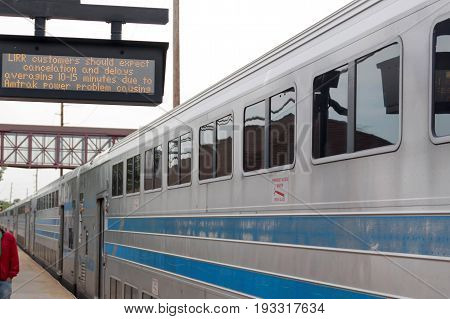 Bay Shore N.Y. USA - 29 May 2017: Train arrives late into Bay Shore with the sign showing cancelations and delays because Amtrak power problems. Twelve tracks lost power at the mid town tunnel.