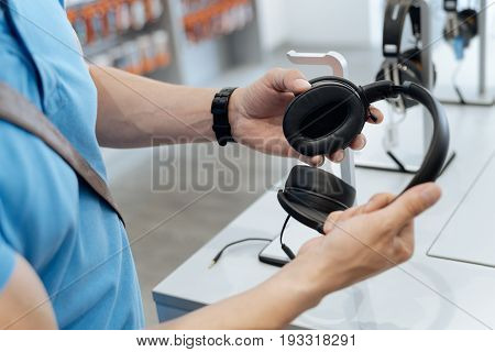 What a beautiful pair. Adult male customer holding and looking at the latest model of headphones while choosing a gift for a friend at a department store.
