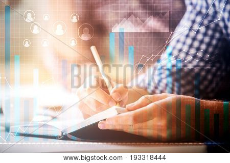 Close up of male hands writing something in notepad placed on office desktop with abstract digital business charts. Statistics concept. Double exposure