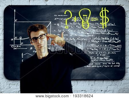 Thoughful businessman with head put to temple as a gun standing in front of chalkboard with mathematical formulas. Idea concept
