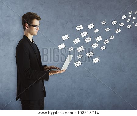 Side portrait of handsome young businessman using laptop on concrete background with drawn letters. E-mail network concept