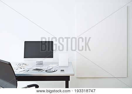 Doctor's desktop with blank computer and other items in concrete interior with empty poster on wall. Mock up 3D Rendering