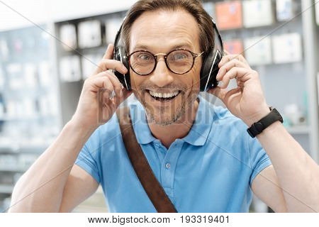 In love with these. Positive male shopper cannot keep his emotions inside while listening to music wearing a pair of template headphones at an electronics shop.