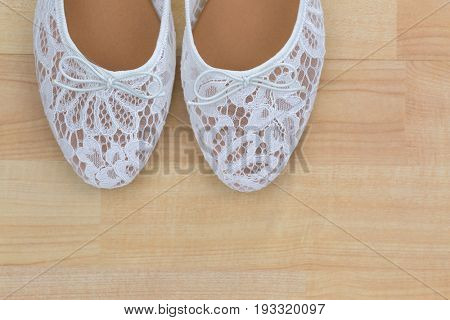 Top partial view of popular white floral lace ballet flat slip on shoes on wooden background with copyspace