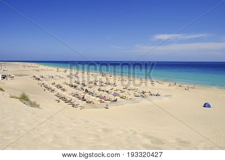 Aerial view on the beach Morro Jable with sand dune sun umbrellas and wonderful water colors of the Atlantic ocean. Canary Island Fuerteventura Spain.