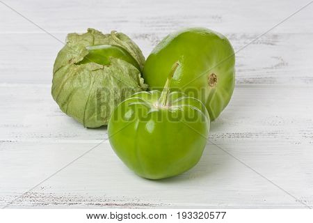 Three whole tomatillos on a painted white background.