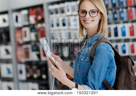 Female shopper smiling while standing at a display and posing with a template smartphone and a product information plate for the camera.