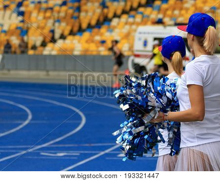 Girls from a support group with pompoms in the stadium.