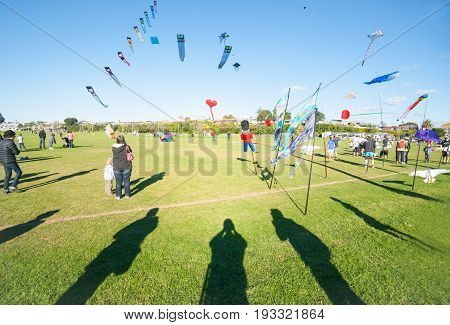 Tauranga, New Zealand - June 4, 2017; Kite flying day foreground shadows of on-lookers photographing colourful array of flying objects and people at Fergusson Park Tauranga New Zealand.